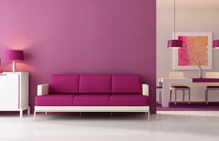 Couch in Lila mit einem Esstisch im Hintergrund, ebenso mit Lila Dekoration