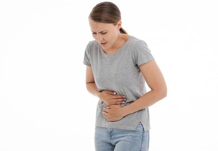 Frau steht vor weißer Wand und hält sich den schmerzenden Bauch