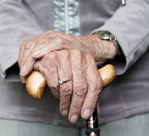 Alte Frau stützt sich auf Ihren Gehstock