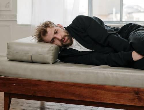Mann liegt mit Bauchschmerzen auf einem Sofa