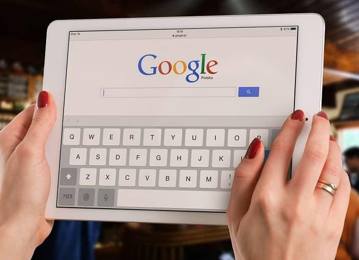 Frau hält ein Tablet in der Hand, die Google Suchmaske ist zu sehen