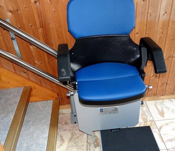 Man sieht einen Treppenlift mit einem blauen Sitz