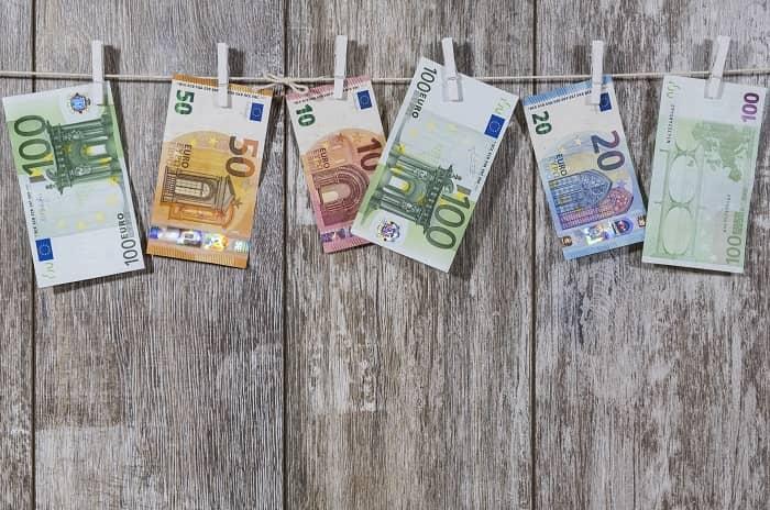 Geldscheine hängen an einer Wäscheleine vor einer grauen Holzwand