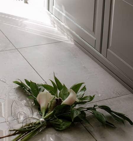 Ein blumenstrauß liegt auf dem boden, daneben die gebrochene Glasvase
