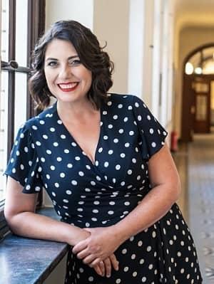 Nina Deissler steht in die Kamera lachend, auf ein Fensterbrett gelehnt, in einem großen Gang. Sie trägt ein schwarzes Kleid mit weißen Punkten
