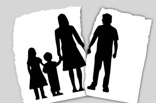 Ein Blatt Papierfast zerissen zwischen Vater und Mutter. Die Mutter hat zwei Kinder an Ihrer Seite