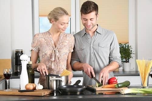 Ein Paar steht in der Küche und kocht zusammen