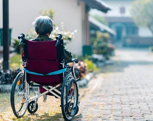 Frau sitzt im Rollstuhl und sieht über eine lange Einfahrt zu Ihrem Hauseingang
