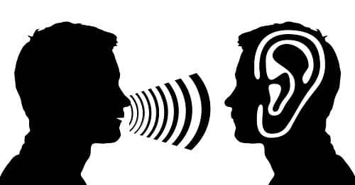 Grafik, ein Mann spricht, ein anderer Mann mit Hörgerät hört zu