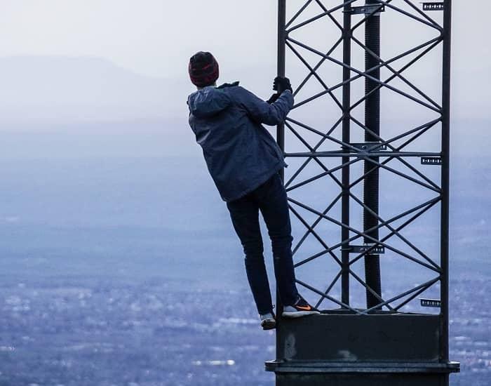 Mann steht hoch auf einem Strommast und blickt übers Meer auf eine gegenüber liegende Landschaft