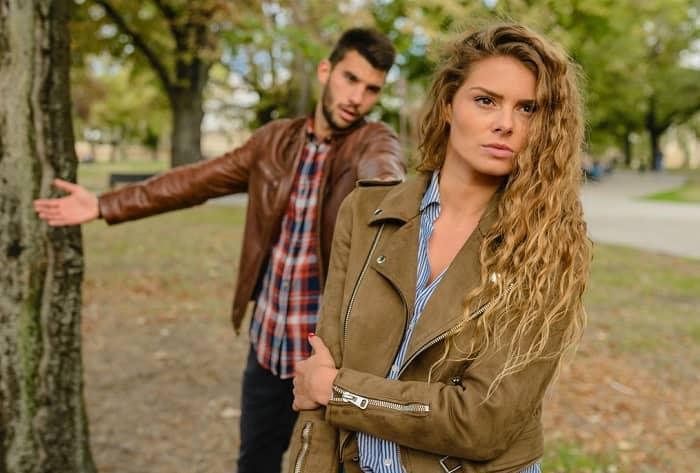 Ein Paar streitet sich in einem Park, die Frau geht weg