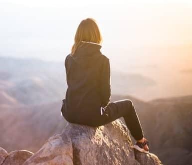 Frau sitzt auf einem Berggipfel und blickt in die Ferne