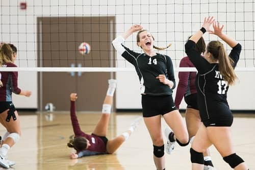 Junge Frauen spielen mit großer Freude Volley Ball