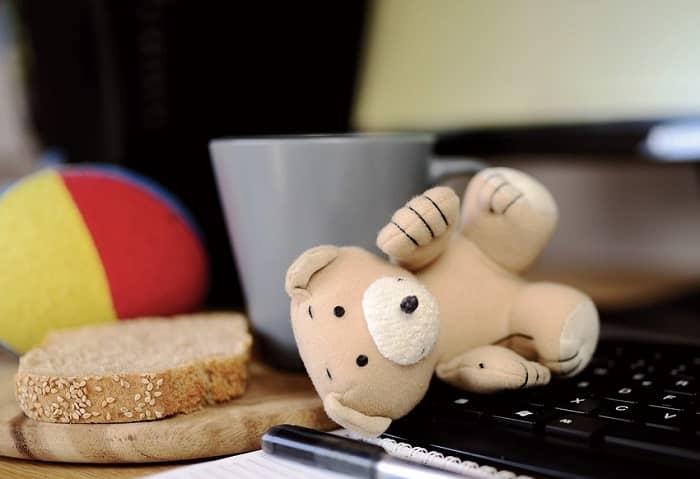 Ein umgefallener Teddy liegt auf einer Computertastatur, daneben ein Brot und ein Kaffeebecher
