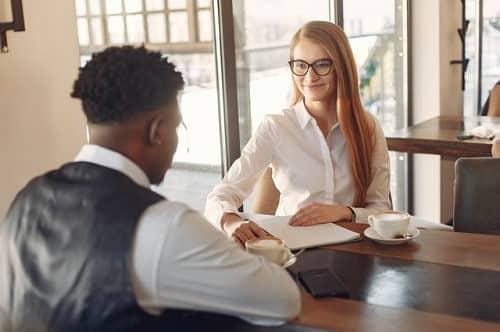 Ein junger Mann stellt sich bei einer Frau im Büro vor