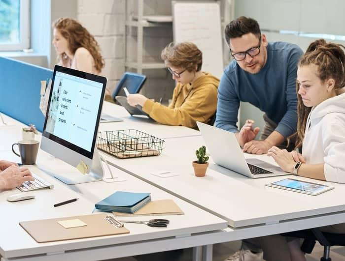 Ein Mann spricht mit einer Frau, in einem Büro wo mehrere Personen an Bildschirmen sitzen