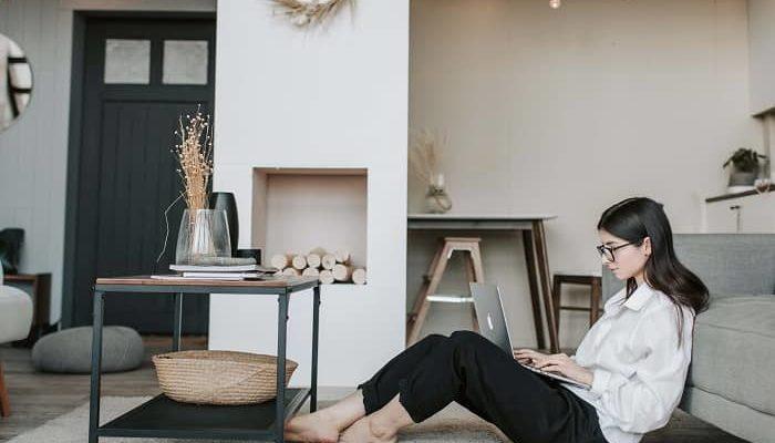Junge Frau sitzt mit Laptop in einem sehr großen Wohnraum