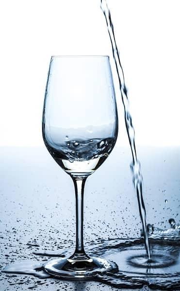 Wasser wird neben ein Glas gegossen