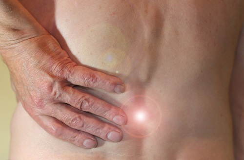 Person greift sich an den unteren Rücken wegen Schmerzen in der Lendenwirbelsäule