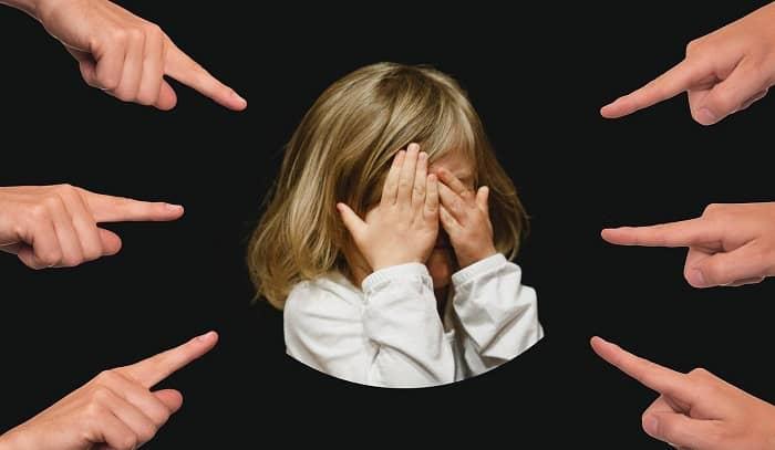 Finger zeigen auf ein kleines Mädchen, das sich hinter Ihren Händen versteckt