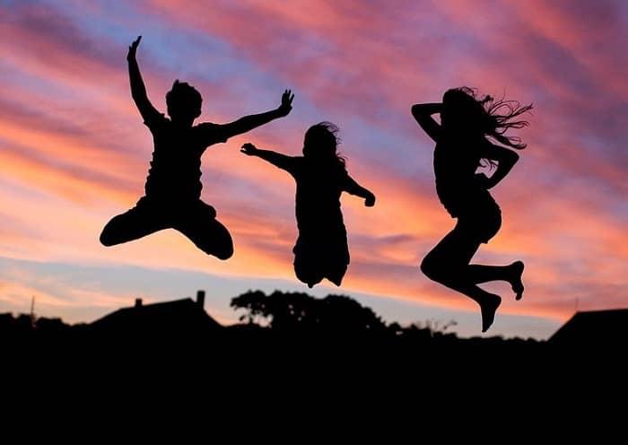 Drei Kinder springen im Abendrot Trampolin im Garten
