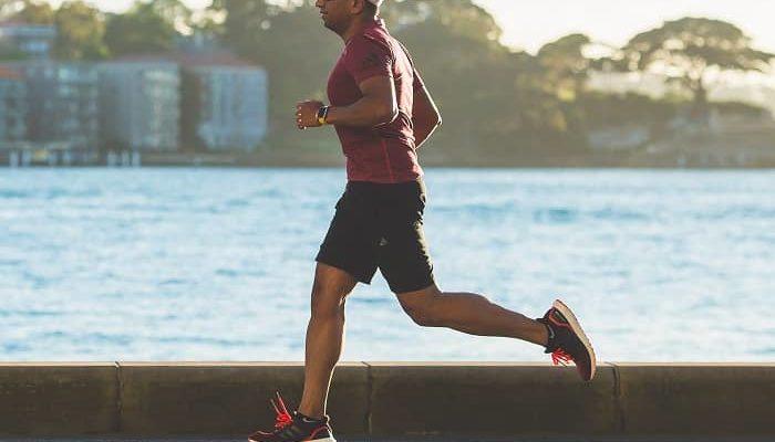 Mann joggt auf einer Strasse am Meer