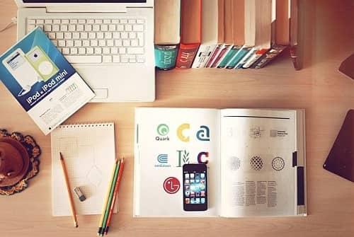 Ein Laptop mund ein aufgeschlagenes Buch mit einem Handy liegen auf einem Schreibtisch