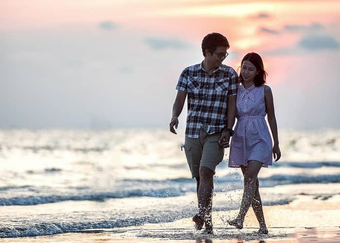 Ein junges Paar geht am Strand durchs Wasser und unterhält sich