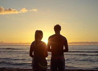 Ein Paar sieht vom strand aus in den Sonnenuntergang und spricht miteinander