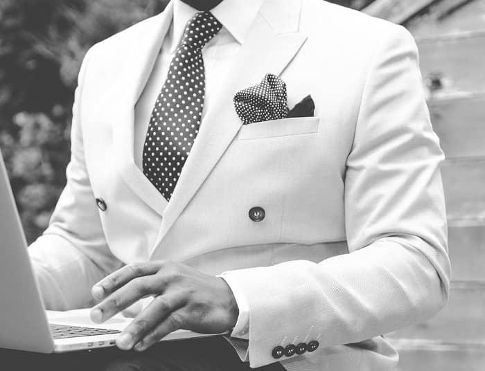 Perfekt gekleideter Mann, mit weißem Sakko und Einstecktuch, sitzt am Laptop
