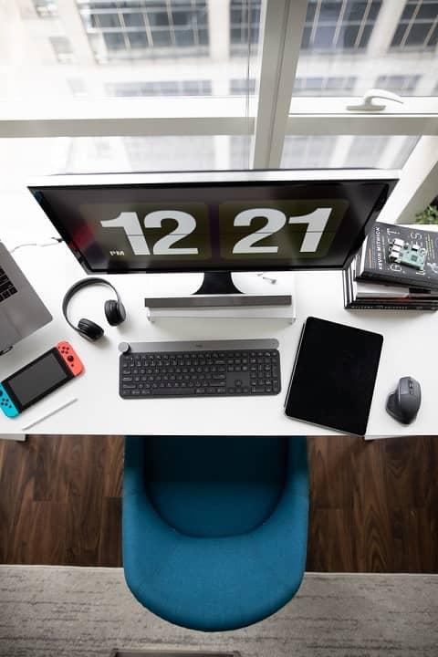 Ein Computerarbeitsplatz mit Bildschirm, Tastatur, Tablett und Kopfhörer wird von oben gezeigt