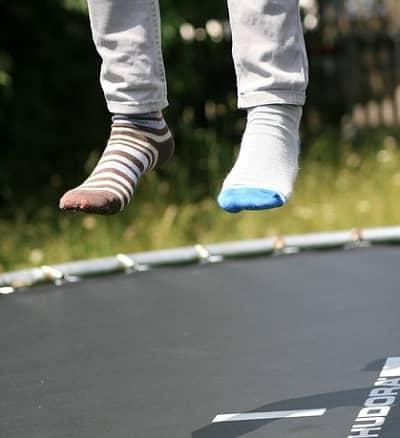 Zwei füße mit unterschiedlichen Socken, springen im Garten Trampolin