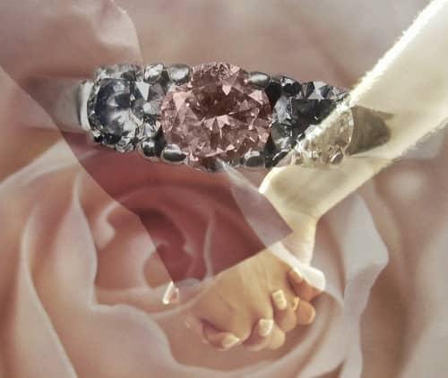 Ein Ring mit rötlichem Rubin und weißen Diamanten, vor ineinander verschlungenen Händen eines Paares