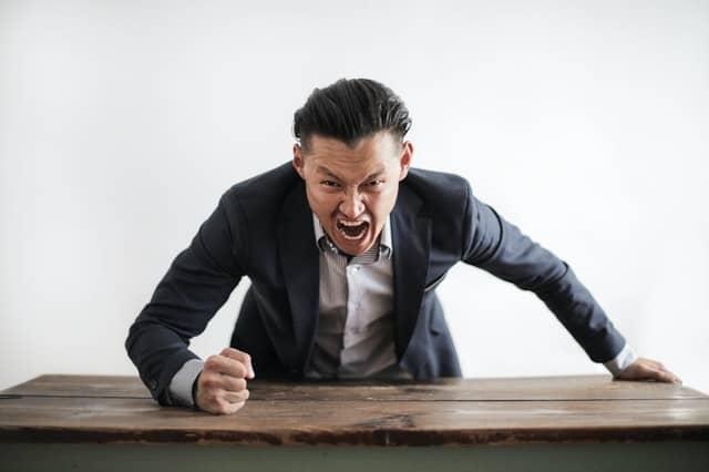 Wütender Mann lehnt sich aggressiv und angriffslustig über einen Tisch