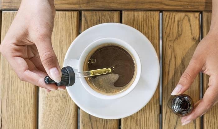 eine Frau tropft CBD Öl in Ihren Kaffee