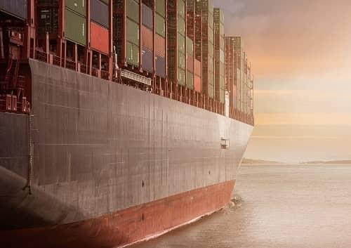 Ein riesiges Containerschiff fährt auf dem Meer Richtung Hafen