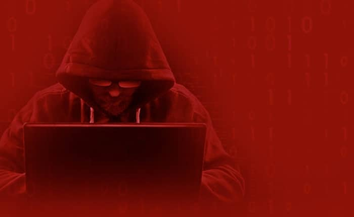 Hacker sitzt mit Laptop und vermummt, vor rotem Hintergrund und diversen Zahlenreihen