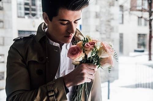 Mann steht mit einem Blumenstrauß vor einem Haus