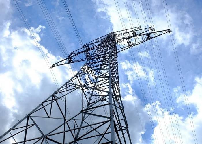 Man sieht von unten einen riesigen Strommasten, der in einen bewölkten, sonnigen Himmel ragt
