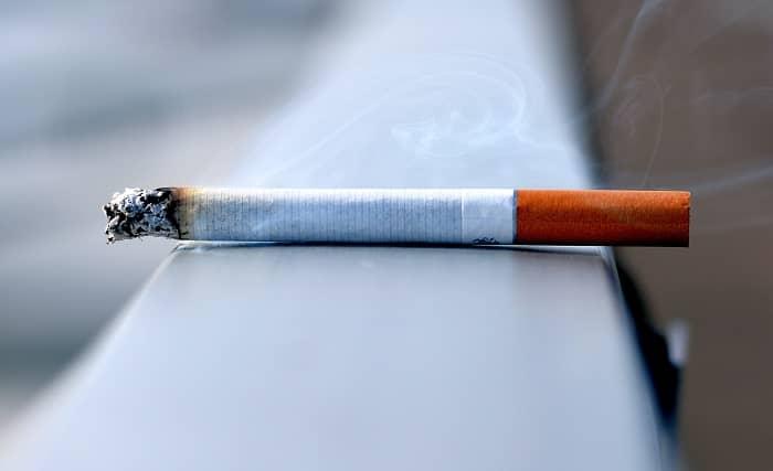 Eine rauchende Zigarette liegt auf einem Brückengeländer