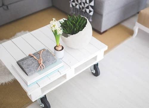 Ein weißer Couchtisch steht neben einer grauen Couch und einem beigen Hocker, er ist mit Blumen dekoriert