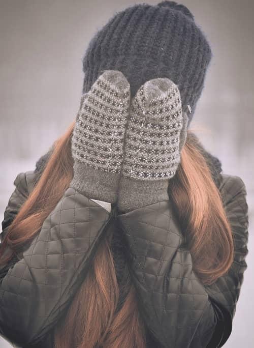 Dick und warm eingepackte Frau hält sich die Hände mit Handschuhen vor das Gesicht