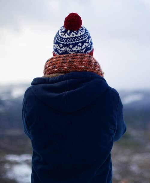 Frau steht warm angezogen auf einem Berg und schaut auf eine gegenüberliegende Bergkette