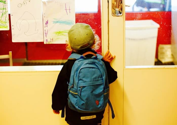 Jung steht vor einer Klassenzimmertür mit einem blauen Rucksack als Schulranzen am Rücken