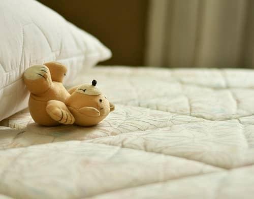 Ein kleiner Plüschteddybär liegt auf einer Matratze mit seinen Füßen am Kopfkissen