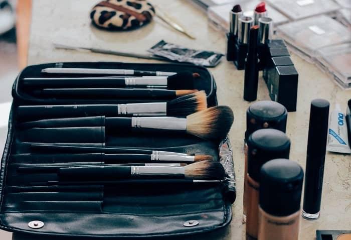 Auf einem Schminktisch liegen verschiedene Schminkutensilien, wie: Pinsel, Lippenstifte und Make ups