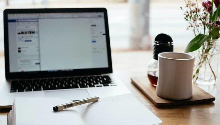 Ein Laptop mit einem Kalender davor stehen auf einem Tisch