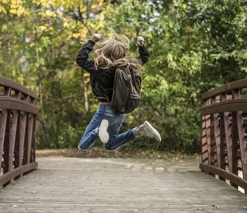 Mädchen springt auf einer Brücke im Park, mit Ihrem Schulranzen am Rücken, vor Freude in die Luft
