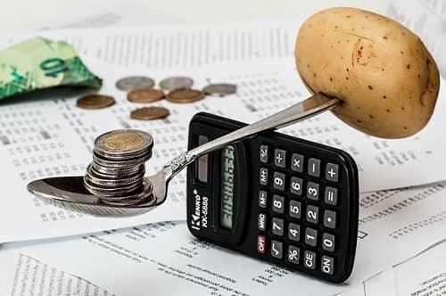 Waage auf einen Rechner mit Geld und einer Kartoffel als Gegengewicht