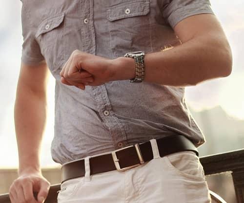 Ein schick gekleideter junger Mann mit einer Luxusuhr am Arm
